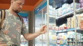 jogurt : Male visitor of supermarket is looking on racks with milk products. He is opening doors and taking yogurt, putting it in his trolley Wideo