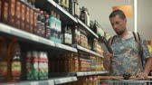 virgem : Adult bearded man is examining inscriptions on bottle with olive oil in a supermarket. He is taking it from shelf, spinning in hands and looking