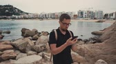гелий : Handsome guy is watching photos and typing on smartphone outdoors in twilight. He is standing on stones sea coast near small resort city