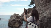 fotografieren : Side view shot of a stylish american tourist in sunglasses taking photos of azure sea and wild nature on vacation. Fantastic landscape view. Stock Footage
