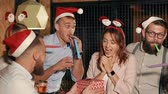 gratulál : Colleagues are giving Christmas gift for young woman on party. One man is closed her eyes, other is giving it, everybody are congratulating