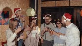 klick : Company of young people are clinking glasses with drinks after toast of bearded man. They are celebrating Christmas and New year, drinking cocktails