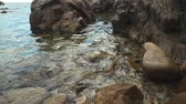sea caves : View on wet solid rocks on sea coast, waves are washing them, close-up. Calm nature on sea shore, nobody