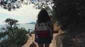 cestování : Female traveler is walking alone on path on mountain and looking on sea from top. She is carrying small backpack, enjoying good weather, back view Dostupné videozáznamy