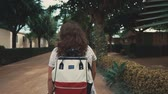 rehber : Back shot of a woman with red and white backpack on a walk in city, looking around on a trip. Brunette female tourist on vacation abroad.