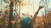 l air : Shot from behind of a woman enjoying warm sunny day in forest in autumn, throwing leaves in the air. Happy day outdoor in beautiful nature.