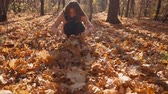 l air : Attractive young girl collecting a pile of a leaves and throwing them in the air jumping high in autumn forest. Beautiful and fun day outside. Vidéos Libres De Droits