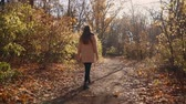 tranquilo : Beautiful back view of a lonely girl walking around in autumn forest, looking at nature. Enjoying nature views.
