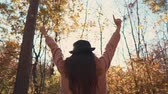 l air : Back view of a stylish girl in a black hat raising her hands in the air outdoor, enjoying fresh air. Woman spending beautiful day in nature in autumn. Vidéos Libres De Droits