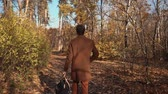 cestování : Shot from behind of a stylish guy walking around in a beautiful autumn forest carrying a backpack, watching around. Relaxing morning walk in forest.