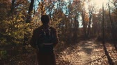 cestování : Shot from behind of a guy with a backpack peacefully walking in woods in fall, looking at beauty of nature. Man takes a walk in forest alone. Dostupné videozáznamy