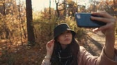 conforto : Clsoe-up shot of a beautiful stylish girl in a black hat taking a selfie on a smartphone in autumn forest, happy face. Lovely smiling woman in woods in fall.