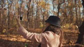 conforto : Female blogger taking a walk in a forest and shooting herself on video on a smartphone alone, lovely day outdoor. Happy day outside in nature in fall.