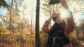 conforto : Charming girl shooting herself on a smartphone in a beautiful autumn forest in a daylight, sun shines on the background. Stylish girl taking selfie outdoor.