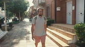 mochila : Male traveler is walking alone in sunny day in outskirts of city. He is viewing on sides, stepping along brick private houses Archivo de Video