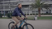 broadly : Bearded guy is driving bicycle in park area in summer day. He is smiling broadly, looking back Stock Footage