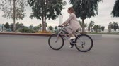 ciclista : Young woman is riding bicycle in summer day. She is rotating pedals and moving to work, side view