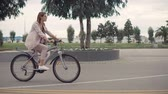 ciclista : Charming girl is driving bicycle in city road. She is enjoying sporty activity and picturesque landscapes
