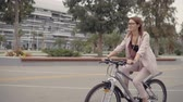 ciclista : Happy young woman is driving a bike in small city. She is using bicycle to move in town, ecological and contemporary private transport