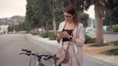 ciclista : Young woman is using smartphone in city street. She is parked her bike and standing near, sending messages