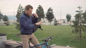 ciclista : Young bearded man is sitting on parked bike, looking around in park. He is taking electronic touchpad from bag and sending messages
