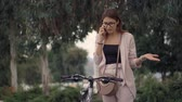 жестикулируя : Pretty emotional woman is calling by phone, speaking loudly and indignantly. She is standing near her bike in street of city, gesticulating Стоковые видеозаписи