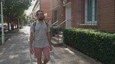 cestování : Urban guy in glasses walking with backpack in hot country, summer vacation walk alone. Man walking on empty street.
