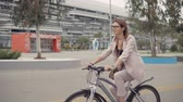 ciclista : Side view of a adorable girl in glasses and light pink costume enjoying peaceful ride on a bike. Woman riding in city on wheels.