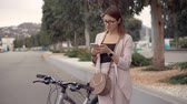 ciclista : Attractive woman in glasses resting during walk on a bike. Girl sitting on a bicycle and sms texting on a smartphone.