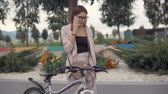 ciclista : Portrait of a girl in glasses having a conversation over phone outdoor, bike standing by her. Woman resting after ride on a bike talking on smartphone.