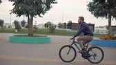 bisiklete binme : Side view shot of a man with a beard on a bicycle ride in city, free ride on empty streets. Outdoor activities. Stok Video