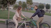 ciclista : Man and a woman meet during bike ride in a park. Friends stop to say hello and keep riding again.