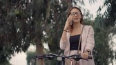 ciclista : Beautiful woman in glasses using smartphone for conversation during walk on a bike. Girl talking to friend over phone.