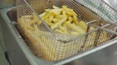 kochen : Chips are deep-frying inside boiling oil in professional fryer in restaurants. Cook is shaking grid, closeup view Stock Footage