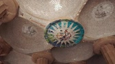 необычный : Fantastic and unusual decoration from ceramic pieces on ceiling of old building. The ceiling of the hall of hundred columns in Park Guell