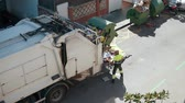sanitation : Refuse truck is lifting garbage container automatically and pouring waste inside. Male worker is standing near and controlling