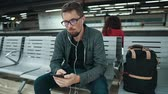 telemóvel : Young guy is sitting in metal bench in metro station in Barcelona, listening music by smartphone. He is using wire earphones, moving head rhythmically