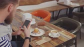 dish photo : Man is using modern smartphone to take photo of cake in restaurant. He is sitting at table, plate with dessert and coffee cup are in front of him