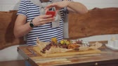 telemóvel : Male visitor of cafe is photographing grilled meat and corn cobs on wooden board. He is using modern mobile phone, view from side