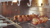 codorna : Close-up on a several meat skewers rotating in a restaurant grill, chicken and bacon rolls. Cooking kebab. Roasted stuffed meat.