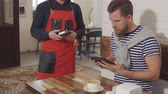 кафетерий : Handsome man in striped tshirt paying for meal with credit card. Man opens his wallet and takes out a card, cashless payment. Стоковые видеозаписи