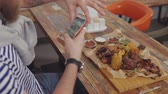 dish photo : Close-up of a man taking different photos of meat dish on table in cafe. Food pictures on smartphone. Beautiful roast meat with vegetables. Stock Footage