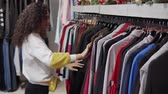 ハンガー : Happy brunette woman is moving in clothing store sale area. She is touching hangers on racks and examining assortment of warm clothes