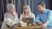 moslem : Two women and man are sitting in cafe in daytime and talking cheerfully. Multiethnic colleagues are resting in break time during working day Stock Footage