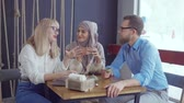 cheerfully : Two arab and caucasian women and their male friend are chatting cheerfully in cafe. They are drinking green tea and gossiping together
