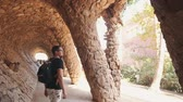 colunata : Man with a backpack walking and looking at a beautiful architectural landmark of Barcelona. Amazing touristic place - Park Guell. Traveling around Europe. Vídeos