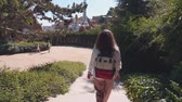 modernism : Shot from behind of a female tourist with stylish backpack going down the stairs in a park. Beautiful Park Guell in Barcelona. Famous park. Urban woman visiting tourist attractions. Stock Footage