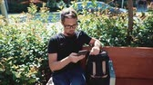 portatile : Smiling man in a black tshirt and backpack resting on a bench in a park, typing on a mobile phone. Handsome guy in glasses spending time outdoor on vacation. Filmati Stock