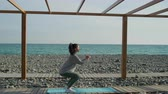 conservar : Slim sportswoman is training alone in beach of sea in daytime. She is doing squats, standing side to camera