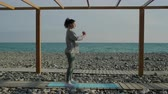 lunges : Female athlete is crouching in beach area of sea in morning. She is holding hands in front of chest, tensing muscles of her body Stock Footage
